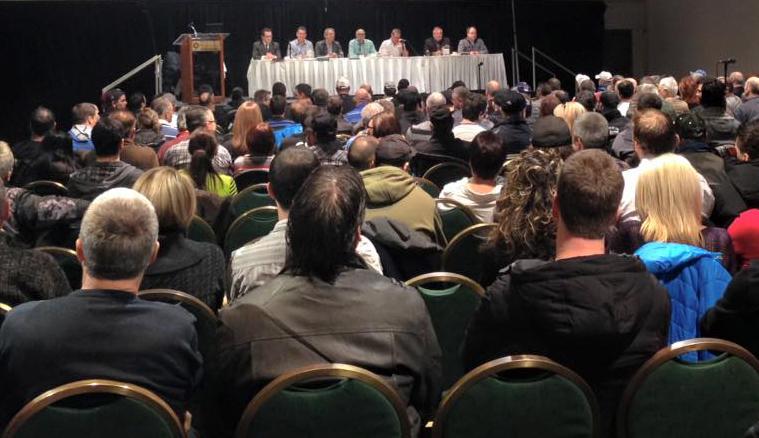 Une foule de personnes sont assises dans une salle