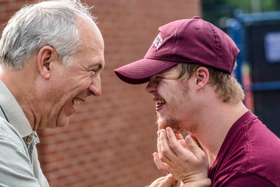 Personne âgée riant avec une personne atteinte de la trisomie 21