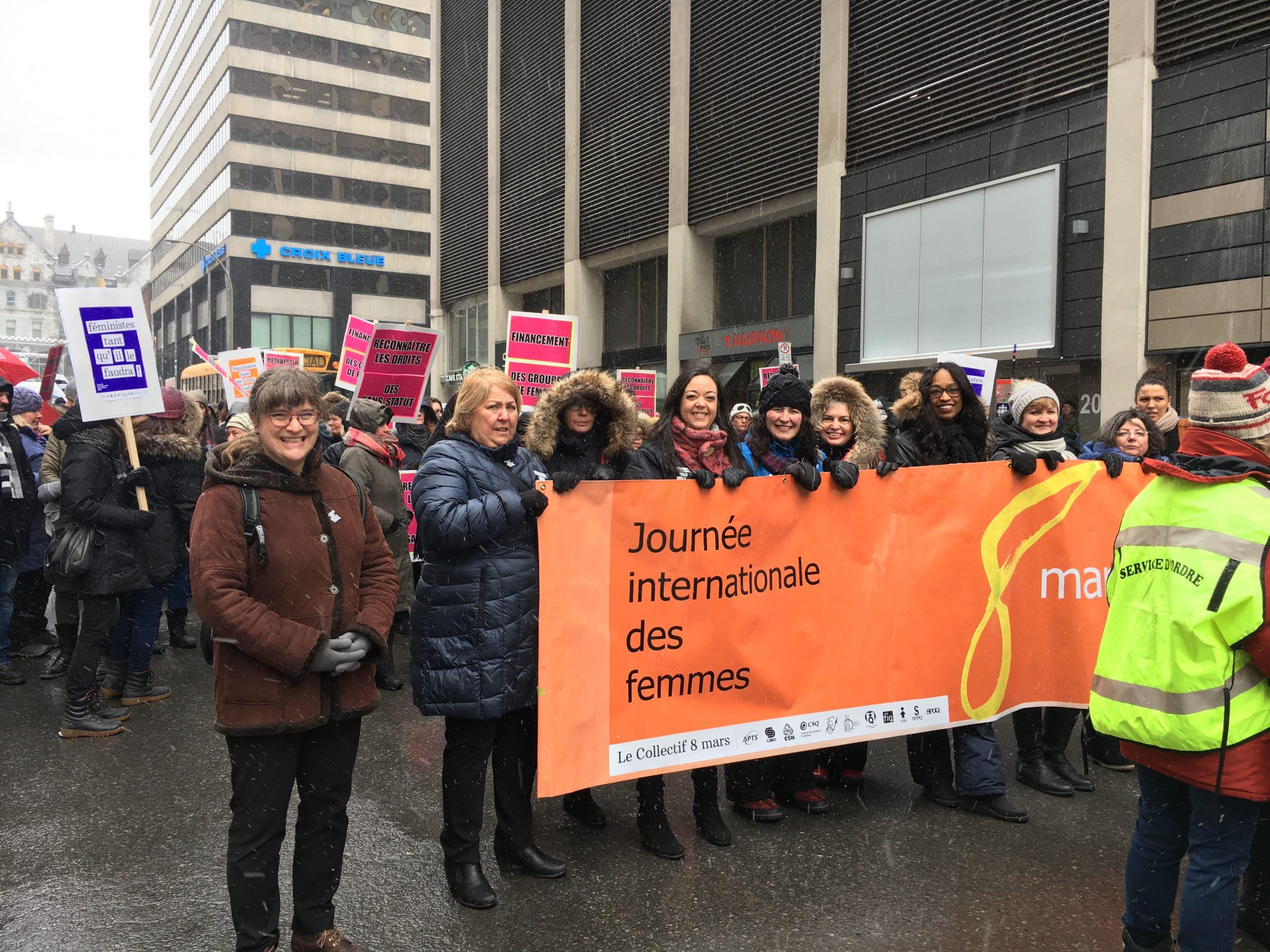 Femmes dans une manifestation du 8 mars pour les droits des femmes tenant une bannière.