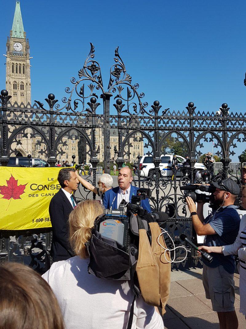 Luc Vachon s'adressant à une foule de journalistes devant le Parlement d'Ottawa.