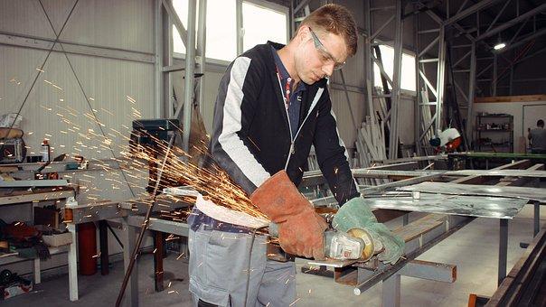 Homme portant un gant en train de travailler le métal.