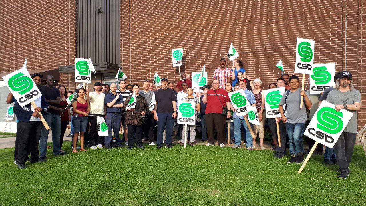 Groupe de militants tenant des pancartes de la CSD devant l'usine Olymel