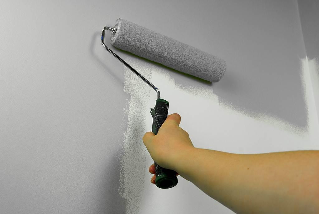 Rouleau de peiture grise sur un mur tenu par une main.