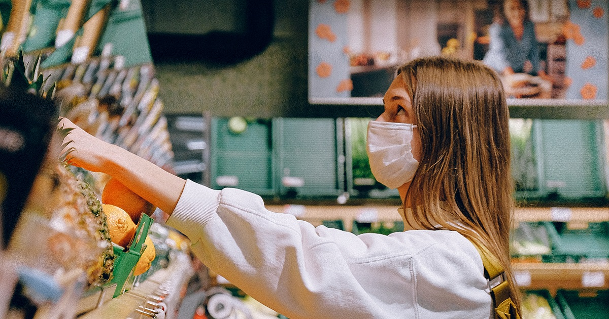 femme travaillant dans une épicerie avec un masque
