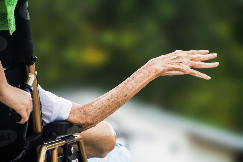 Bras d'une personne âgée sur un fauteuil roulant
