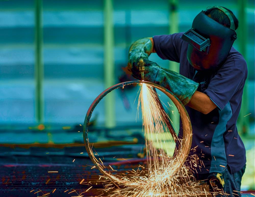 Soudeur portant un masque en train de travailler sur un cercle en métal.