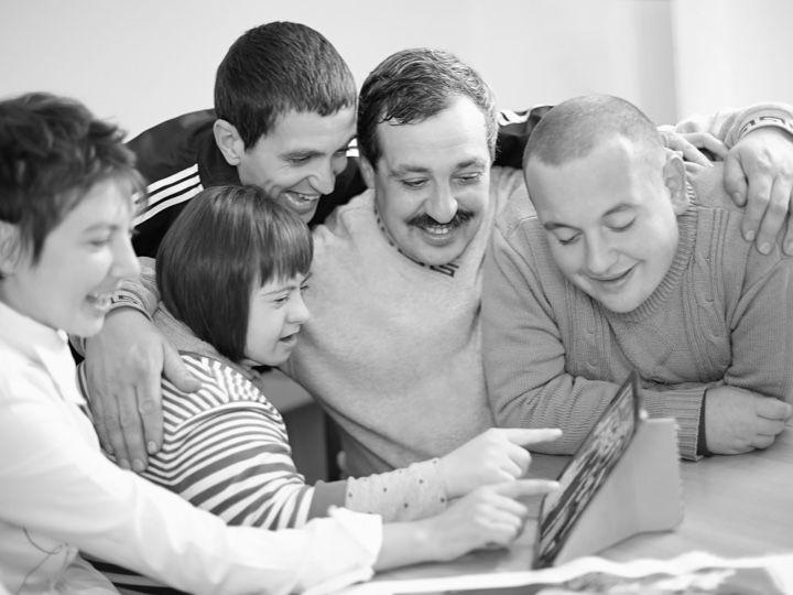 Photo en noir et blanc de plusieurs jeunes regardant un écran.