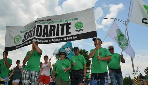 Manifestants du SDEG tenant une pancarte SOLIDARITÉ et des chandails verts à l'effigie de la CSD.