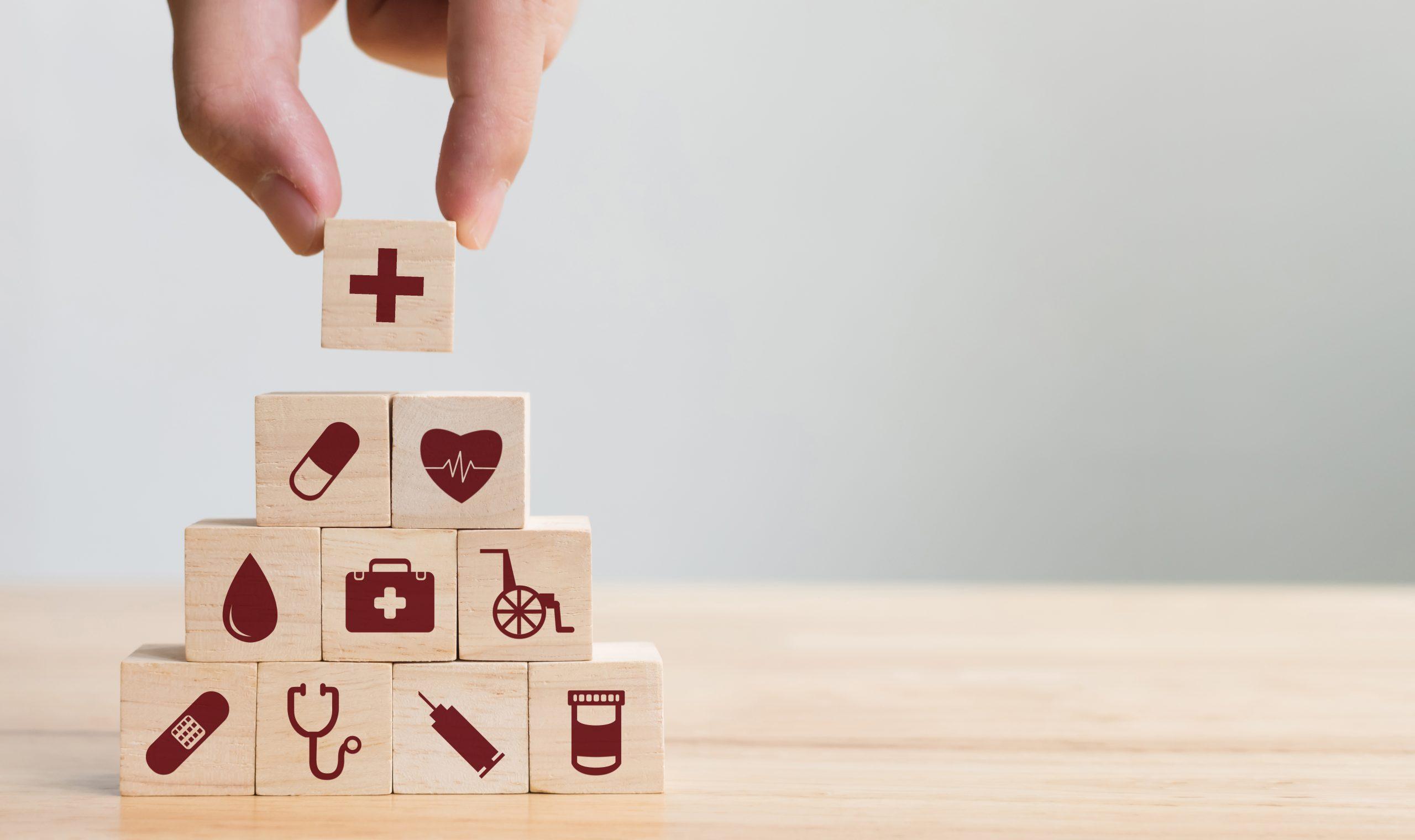 Blocs de bois empilés en forme de pyramide avec des dessins rouge représentants différents éléments de la santé.
