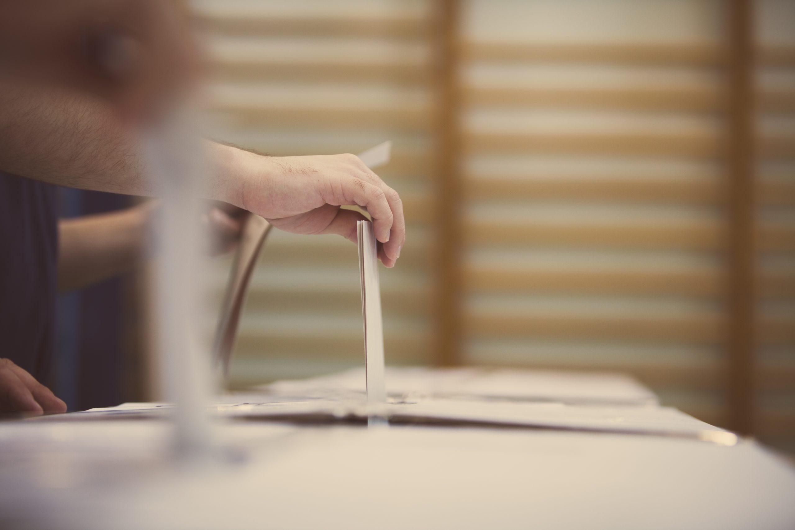Personne mettant un billet de vote dans une boîte