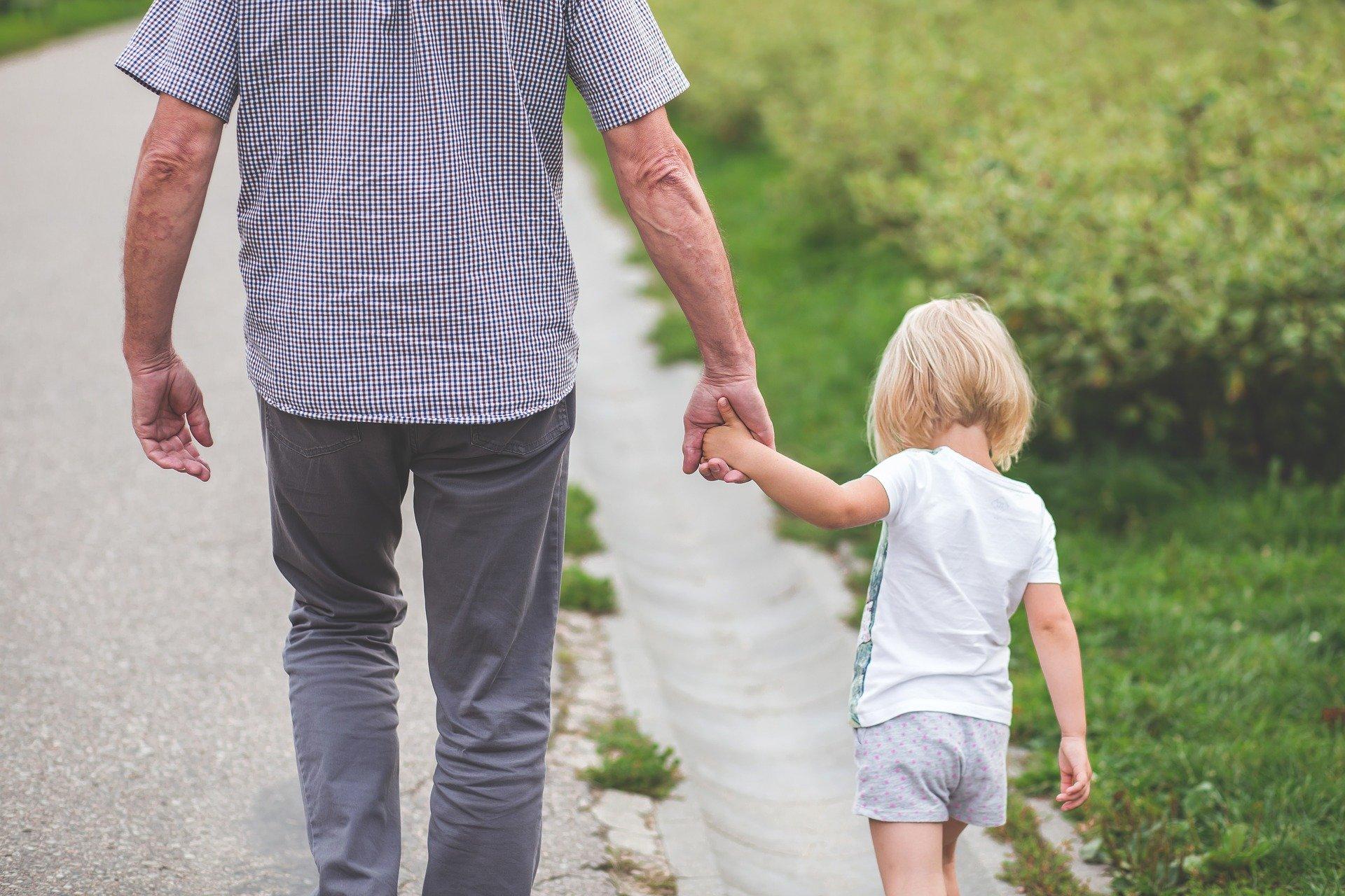Enfant tenant son père par la main