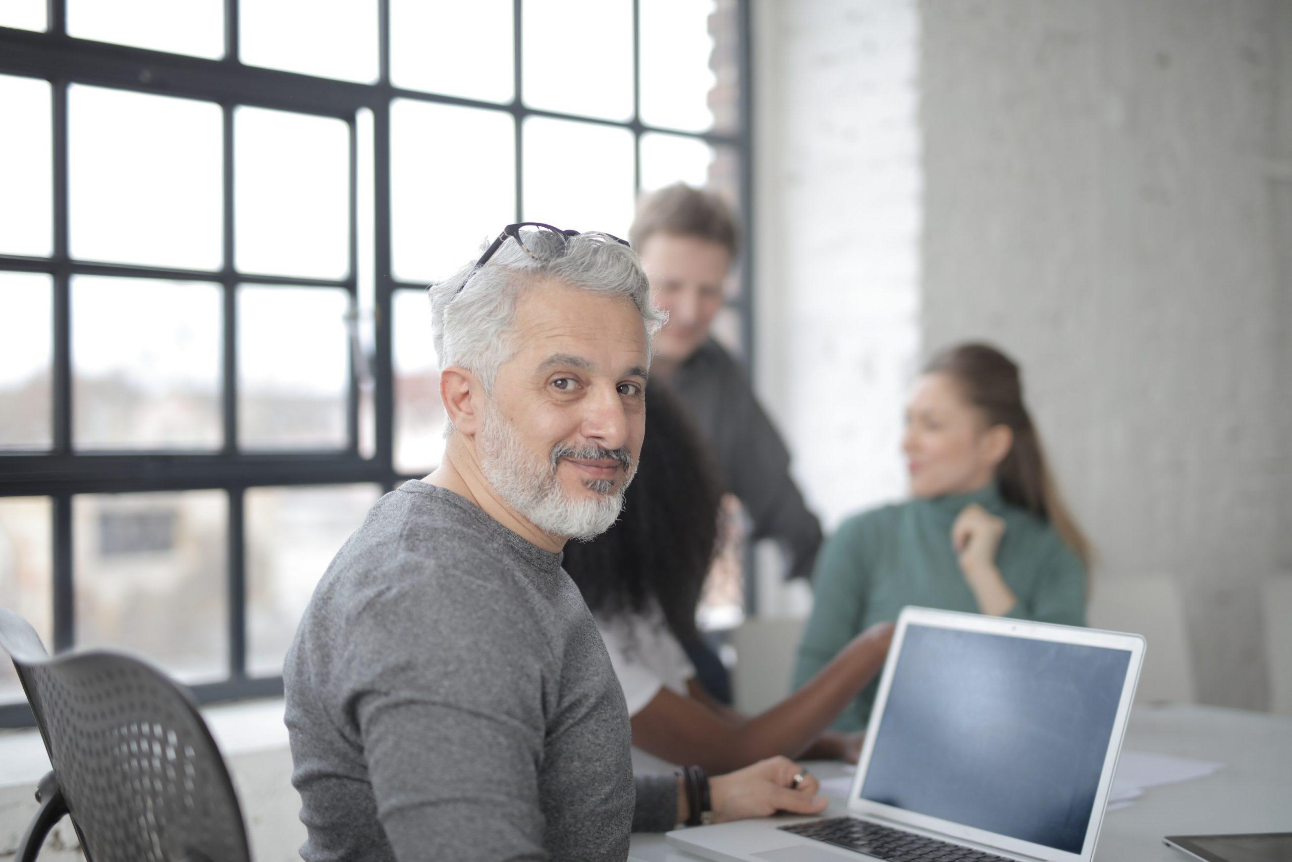 Homme grisonnant devant un ordinateur portable.